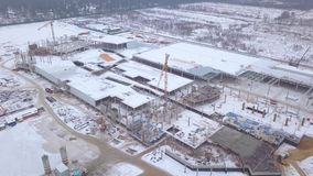 Construction cranes working on construction building aerial view. Drone view tower crane on industrial area at winter construction site stock footage