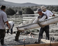 Construction crew placing concrete from a cement truck chute to Royalty Free Stock Photo