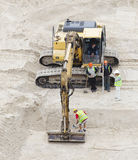 Construction crew working with excavator at building site. Stock Image