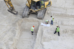 Construction crew working with excavator at building site. Royalty Free Stock Photography