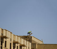 Construction crew working on roof against blue sky Royalty Free Stock Photos