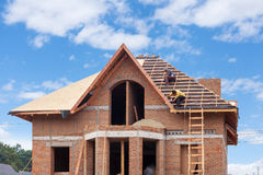 Construction crew working on the roof sheeting of new house made with bricks. Construction crew working on the roof sheeting of new house made with bricks Royalty Free Stock Images