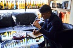 Construction d'un jeune homme attirant de grande carte des vins donnant la recommandation du vin photo stock