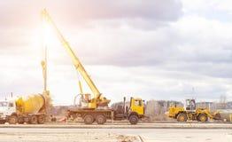 Construction d'une nouvelle route et installation des lampadaires utilisant un camion de grue et de ciment de camion, travailleur photo libre de droits