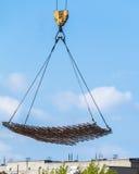 Construction de maison de brique la grue abaisse la charge photo stock