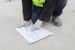 Construction de maison de vue Le travailleur regarde sur le plan de la disposition des panneaux de mur Photos libres de droits