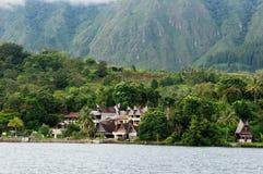 Construction de plusieurs maisons au pied d'une montagne à côté d'un lac en île de Sumatra Samosir Image stock
