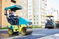 Construction de routes Travailleur sur l'asphalte de compactage de rouleau de vibration de vapeur photo stock