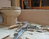 Construction Debris Around A Toilet. In a home renovation. There are broken tiles, faucet, exposed insulation, metal and wood scraps Stock Photography