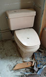 Construction Debris Around A Toilet. In a home renovation. There are broken tiles, faucet, exposed insulation, metal and wood scraps Royalty Free Stock Photo