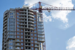The construction of a detached high-rise building. Tower Crane near the new high-rise building Royalty Free Stock Photography
