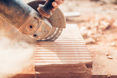 Construction details - close-up of angle grinder cutting through bricks Royalty Free Stock Images