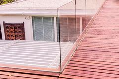 Construction details : Tempered glass balustrades on wooden roof deck. Modern style design Stock Image