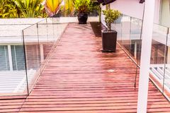 Construction details : Tempered glass balustrades on wooden roof deck. Of modern style villa Royalty Free Stock Image