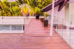 Construction details : Tempered glass balustrades on wooden roof deck. Of modern style villa Royalty Free Stock Photo