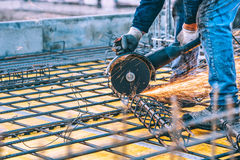 Construction details with worker cutting steel bars and reinforced steel with angle grinder. Filtered image. Industrial details with worker cutting steel bars Royalty Free Stock Images