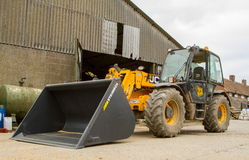 Construction digger loader in farm yard with barn Stock Images