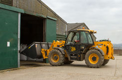 Construction digger loader in farm yard with barn Stock Photo