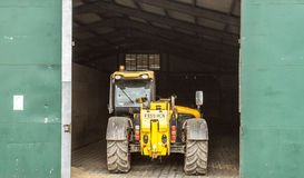Construction digger loader parked in shed Stock Image