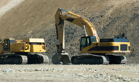 Construction Digging Equipment. Is heavy digging bulldozer type equipment next to a large dirt land mass Stock Images