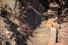 Construction ditch with bricks and plant roots. Construction ditch with red bricks and plant roots stock photo