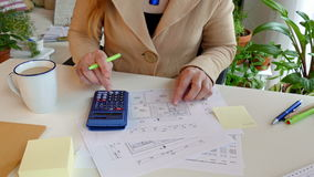 Construction drawing. A woman computes the living space of a house stock footage