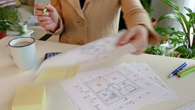 Construction drawing. A woman reaches the construction drawing of a residential building further stock video