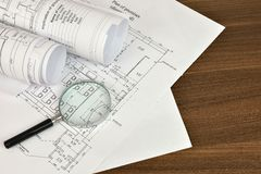 Construction drawings and magnifying glass Stock Images