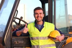 Construction driver with excavator on the background.  stock photo