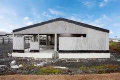 Construction du bâtiment de la nouvelle maison en béton blanche avec le toit en bois inachevé images stock