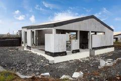 Construction du bâtiment de la nouvelle maison en béton blanche avec le toit en bois inachevé photos libres de droits