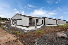 Construction du bâtiment de nouvelles maisons en béton blanches avec le toit en bois inachevé photo stock