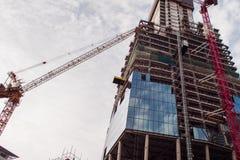 Construction du gratte-ciel Grues et gratte-ciel de construction Photographie stock libre de droits