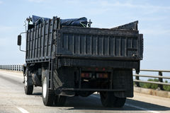 Construction Dump Truck on Highway. Rear and side view of dump and debris construction truck on highway Royalty Free Stock Photos