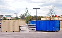 Construction Dumpster. Bright blue dumpster with stacked construction materials in mall parking lot Royalty Free Stock Photo