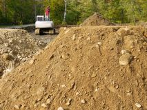Construction: earth piles and backhoe h royalty free stock image