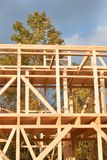 Construction of ecological house. Wooden frame of house under construction.Framed New Construction of a House. Stock Photo