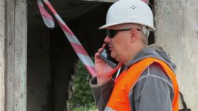 Construction employee with cell phone near damaged building stock video footage