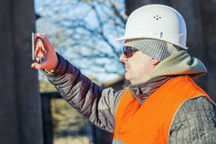 Construction employee filmed with tablet PC. In winter   day Royalty Free Stock Image