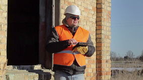 Construction employee with tablet PC near building stock video