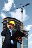 Construction Engineer. Examine a project plan while taking a phone call Stock Photo