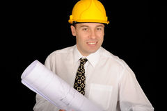 Construction engineer. A studio view of a professional construction engineer or architect wearing a yellow safety hat and holding a set of architectural drawings royalty free stock photography