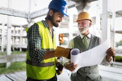 Construction engineer with foreman worker checking construction site. Construction engineer architect with foreman worker checking construction site stock photography
