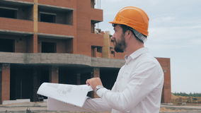 Construction engineer with blueprint working on a construction site. stock footage