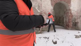 Construction engineer close up using tablet PC with worker in background stock video footage