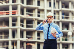 Construction engineer at the construction site looking at the camera and talking mobilephone. Construction engineer at the construction site talking mobilephone Royalty Free Stock Photo