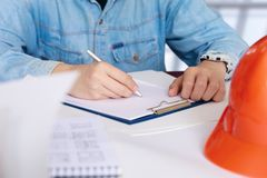 Construction engineer develops a construction plan . Construction engineer develops a construction plan at the Desk in the office Stock Images