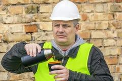 Construction Engineer drinking tea near stone wall stock photography