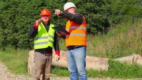 Construction Engineer explains to worker assigned work stock video footage