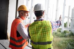 Construction engineer with foreman worker checking construction site royalty free stock photo